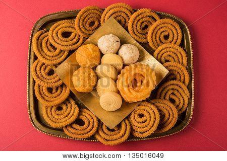diwali snacks chakali or chakli, bundi laddu, jalebi, pedha or pera, coconut laddu in a brass tray over red background, top angle and isolated