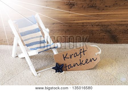Sunny Summer Label With Sand And Aged Wooden Background. German Text Kraft Tanken Means Relax. Deck Chair For Holiday Or Vacation Feeling.