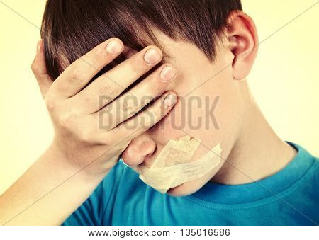 Toned Photo of Sad Kid with sealed Mouth on the White Background