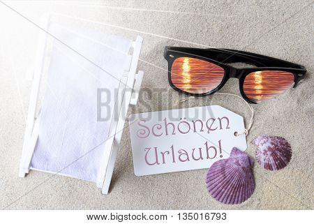 Sunny Summer Label With German Text Schoenen Urlaub Means Happy Holidays. Flat Lay View. Summer Decoration With Deck Chair, Seashells And Sunglasses. Greeting Crad With Sand Background