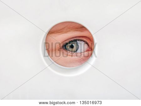 The Child Eye peeking through a Hole