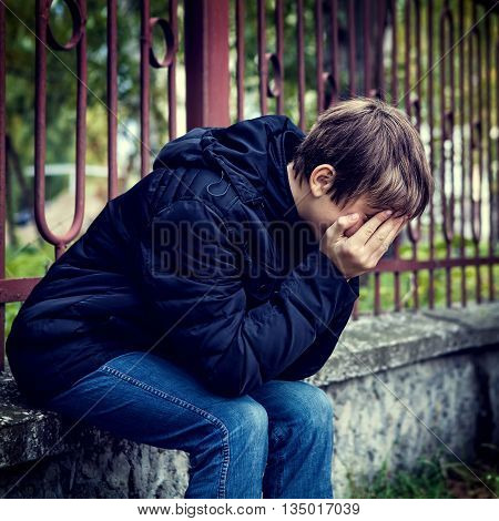 Toned Photo of Sorrowful Teenager sit on the City Street