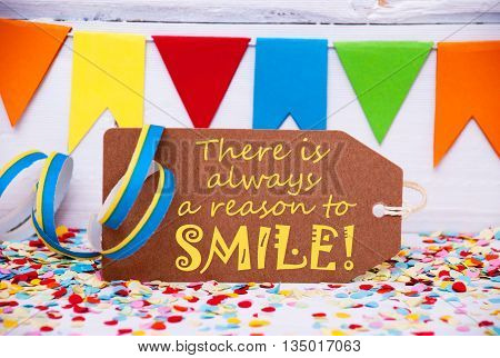 Label With English Quote There Is Always A Reason To Smile. Party Decoration Like Streamer, Confetti And Bunting Flags. White Wooden Background With Vintage, Retro Or Rustic Syle