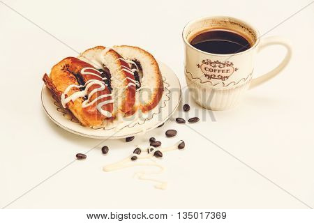 There are Pieces of  Roll with Poppyseed and Condensed Milk,Chocolate Peas,Cap of Coffe;Tasty Sweet Food on the White Background