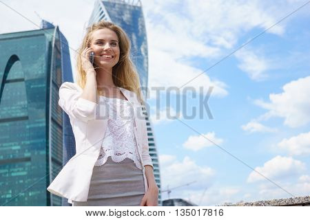 Smiling young business woman having pleasant conversation on mobile phone