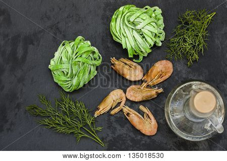 fettuccine with spinach and shrimp on a black background