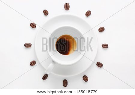 Drunk cup of strong coffee with coffee spent grounds on saucer and coffee beans against white background forming clock dial viewed from above