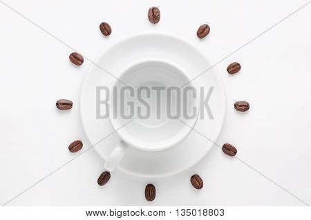 Empty coffee cup on saucer and coffee beans against white background forming clock dial viewed from above