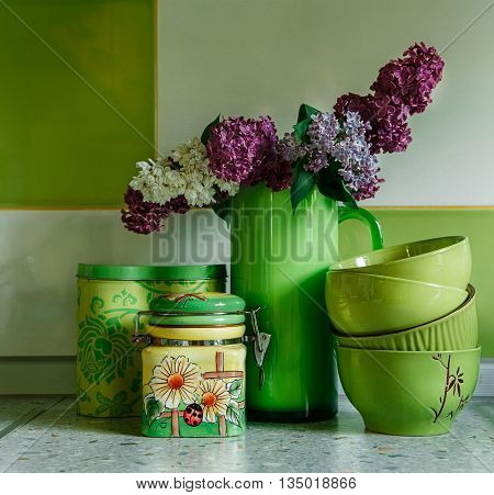 Ceramic Plates and Jars.Tableware Bouquet of Lilac in the Green Pitcher.Kitchen accessories