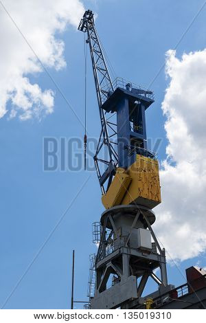 Cargo crane against the blue sky with clouds in the port of Hamburg Germany vertical copy space
