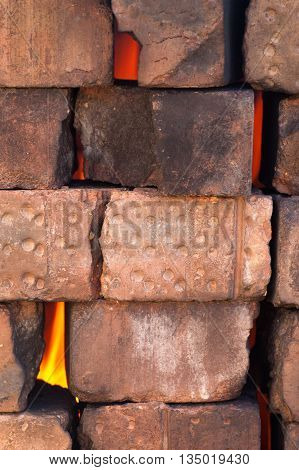 Fire flame behind an old dry masonry wall of burnt bricks vertical image