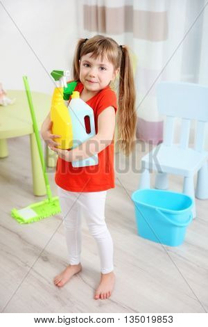 Cute little girl cleaning her room