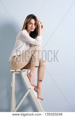 Beautiful young woman sitting on a wooden ladder on blue wall background