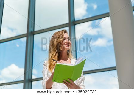Young beautiful woman holding green notebook. Diary concept.