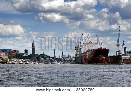 Hamburg Germany - June 11 2016: City of Hamburg and the container ship Montreal Express in a dry dock view from the cargo port in the river Elbe typical cloudy sky copy space