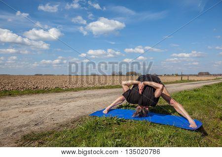 on an sunny day this man enjoys prasarita padottanasana yoga in nature