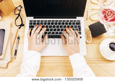 Topview of wooden designer desktop with flowers coffee glasses and female hands typing on computer keyboard