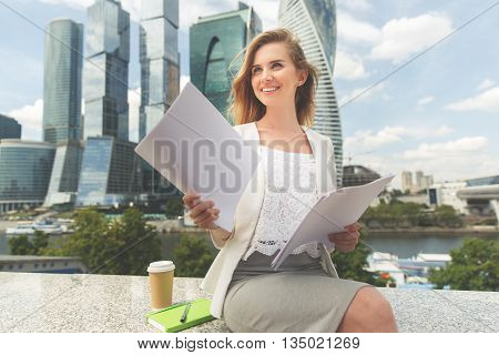 business, paperwork and people concept - young smiling businesswoman with heap of papers sitting on city bench