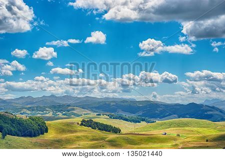 Scenic beauty of Montenegro. Panorama with green field and mountains against the blue sky. Durmitor Montenegro.
