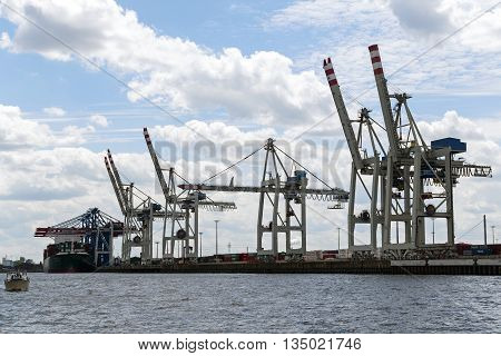 Hamburg Germany - June 11 2016: cranes and a container ship in the international cargo port of Hamburg blue sky with clouds copy space