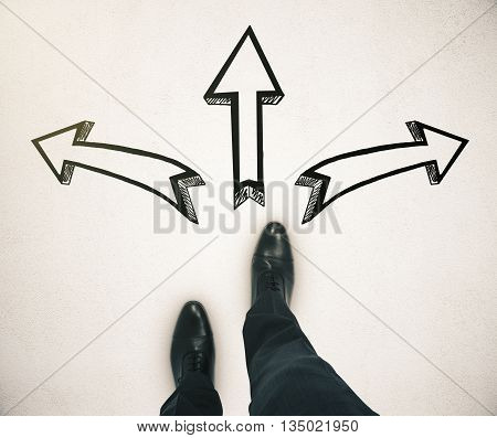Different direction concept with businessman feet and three arrow sketches on light ground