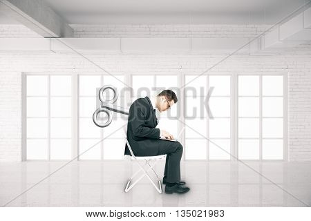 Businessman with a wind-up key on his back sitting on chair and using laptop in white brick room. Concept of control