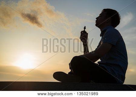 A man smoking vaping e-cigarette vape box mode over golden sunset.