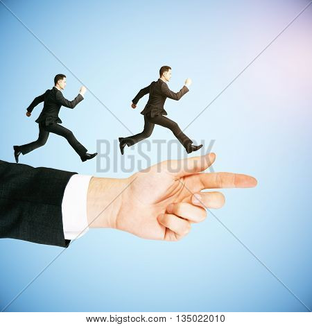 Guidance concept with businessmen running on abstract arm pointing forward on blue background