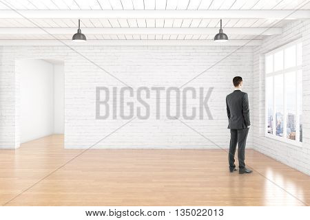 Thoughtful businessman in empty room interior with blank white brick wall wooden floor ceiling and window with city view. Mock up 3D Rendering