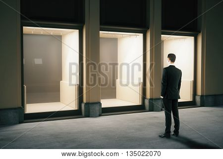 Side view of shop exterior design with glass showcase and looking businessman at night. Mock up 3D Rendering