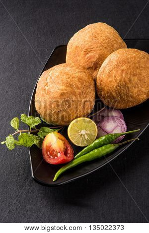Kachori or Kachauri or Kachodi or Katchuri is a spicy snack popular in india, asian snacks, pakistani snacks with green salad and tomato over black background