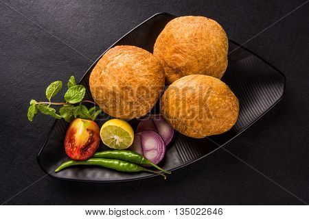 Kachori or Kachauri or Kachodi or Katchuri is a spicy snack popular in india, asian snacks, pakistani snacks with tea and green salad and tomato over black background