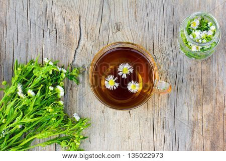glass cup with tea of chamomile a bunch of chamomile flowers pharmacy and a glass jar with a camomile on old wooden table in the cracks close up top view