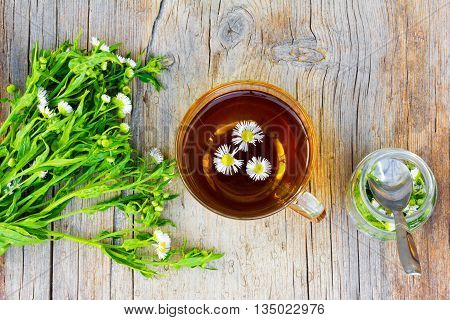glass cup with tea of chamomile pharmacy a bunch of chamomile flowers pharmacy and a glass jar with a spoon and a camomile on old wooden table in the cracks close up top view