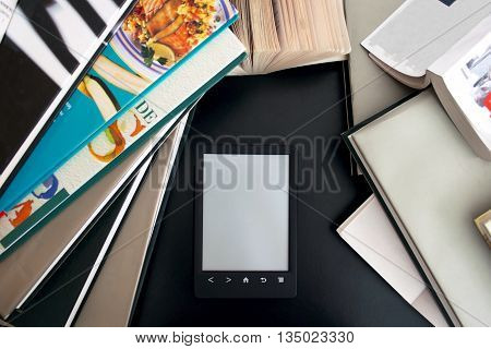E-book with a gray screen on the black table among the many paper books