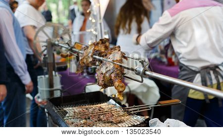Meat barbecue picnic at country fair. Lamb leg roasted at spit. Lamb grill, big piece of meat at rolling skewer. Street vendor, professional Chef cooking food bbq, unrecognizable. Cooking, catering