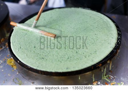Making spinach crepe. Vegetable green crepe or pancake made by street vendor at outdoors creperie. French cuisine, cooking, commercial kitchen.