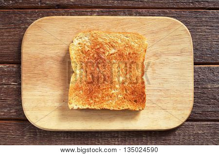 Slice of toasted bread on kitchen board top view