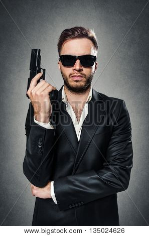 Bearded secret agent wearing a dark suit and sunglasses holding a handgun