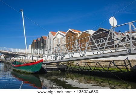 A moored row boat in a canal next to a street in Aveiro, Portugal