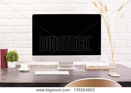 Creative designer desktop with blank computer monitor keyboard coffee cup smartphone stationery and decorative plants on white brick wall background. Mock up