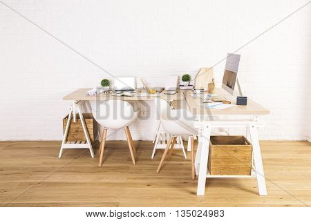 Front view of interior with creative designer workplace wooden floor and white brick wall