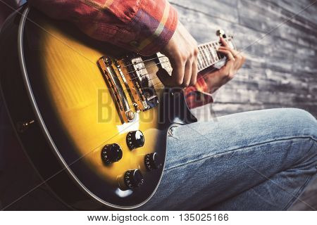 Side view of young casual guy playing electric sunburst guitar on wooden background. Closeup