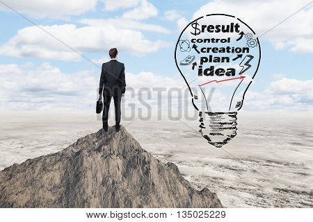 Business idea concept with abstract lightbulb sketch and thoughtful businessman on mountain top looking into the distance