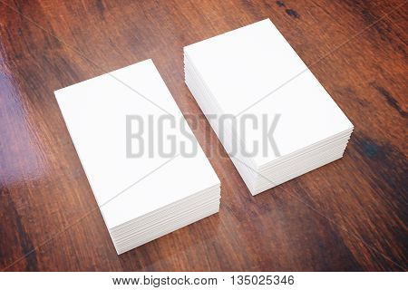 Two stacks of blank business cards on dark wooden surface. Mock up 3D Rendering