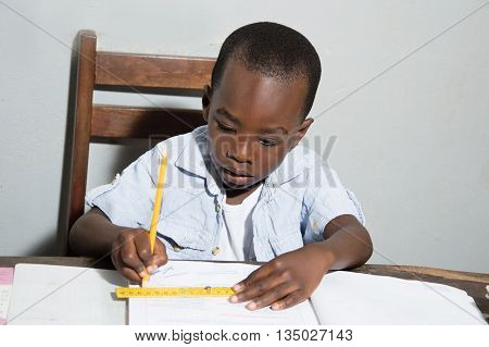 Child draws a line in pencil with a wooden ruler