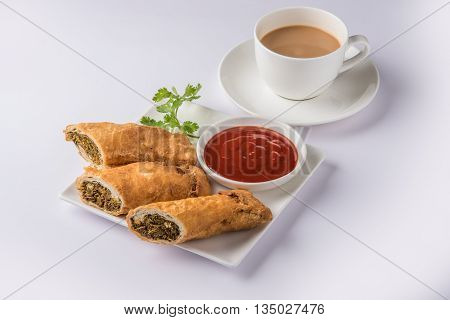 spring rolls or kothimbir vadi or sambar vadi or coriander spring rolls, indian snacks, tastes great with tea and tomato ketchup or tomato sauce, in square white plate over colourful background
