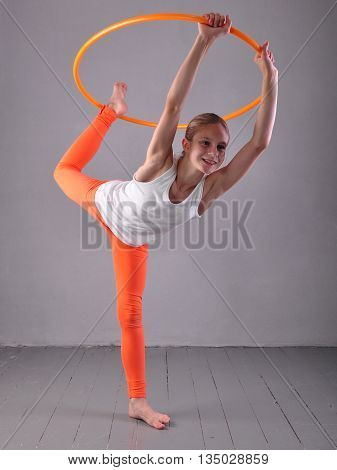 Teenage sportive girl is doing exercises with hula hoop on grey background. Having fun playing game hula-hoop. Sport healthy lifestyle concept. Teenager exercising with tool.