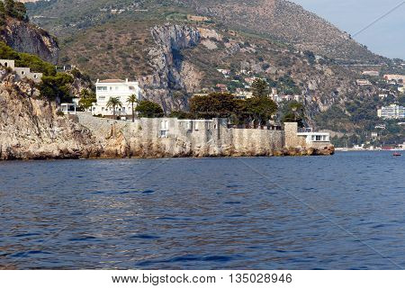 Luxury homes on the rocky Mediterranean coast of the French Riviera. Horizontal with copy space for text