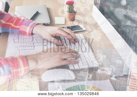 Side view of male hands using computer keyboard on wooden office desktop with construction sketch and other items with abstract city and cogwheels layer